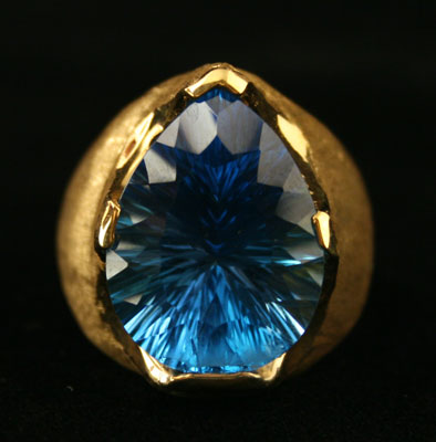 18 Karat Gold Ring with a Florentine Finish Featuring a Blue Topaz